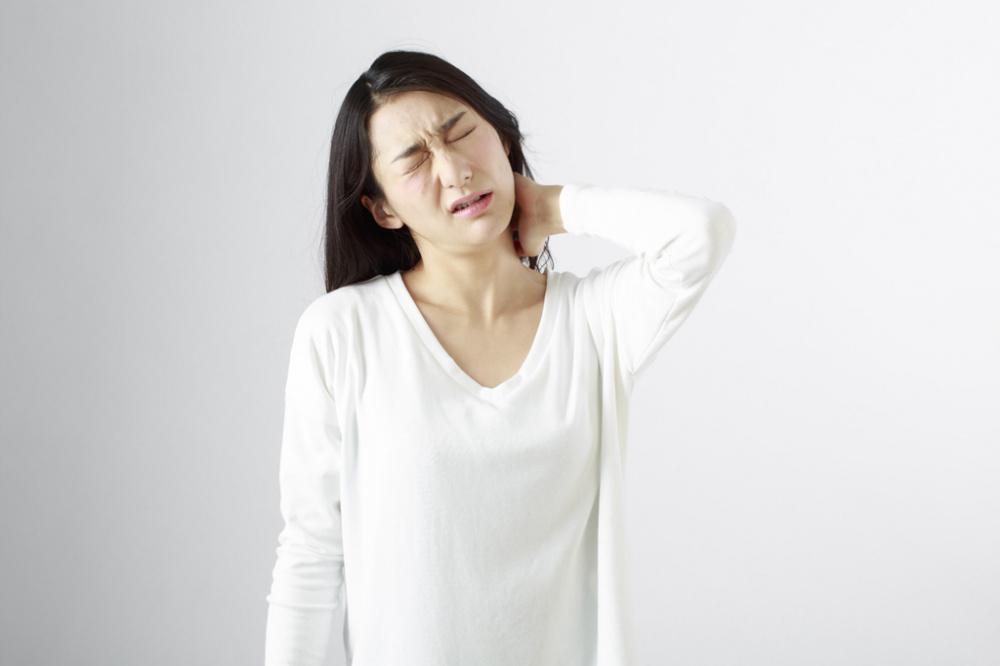 寝違えに苦しむ女性。